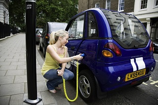 Young woman charging electric car --- Image by © Nancy Honey/cultura/Corbis
